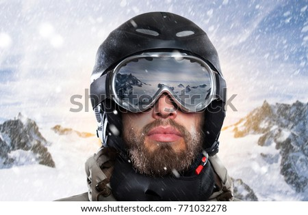 portrait of a snowboarder with helmet and goggles in front of sunrise in wintry mountains landscape while a stormy blizzard #771032278