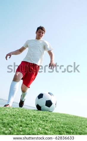 Portrait of a soccer player going to kick ball on football field