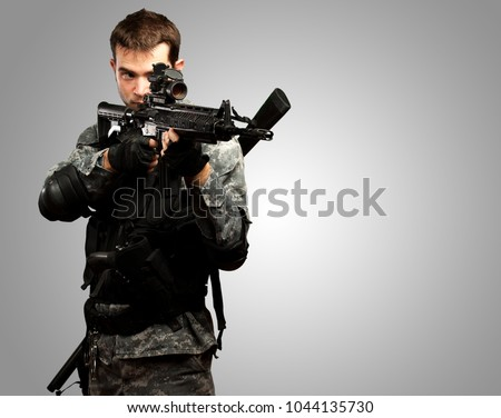Portrait Of A Soldier Holding Gun against a grey background