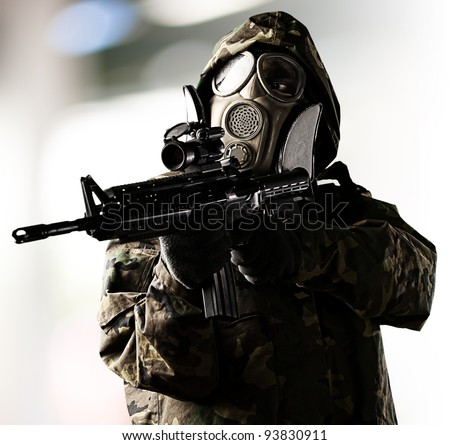 portrait of a soldier wearing a gas mask and aiming with a shot gun indoor