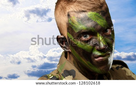 portrait of a soldier with camouflage painting against a cloudy sky background - stock photo