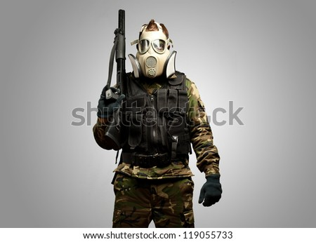 Portrait Of A Soldier With Gas Mask against a grey background