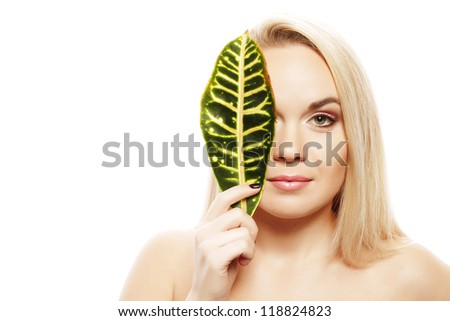 Portrait of a spa woman. Beautiful blonde girl after bath hides a half of her face with a leaf of plant. Perfect skin. Skincare. Young skin. Studio shot
