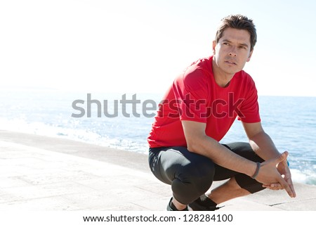 Portrait of a sports man crouching down on a track by the sea on a sunny day, being thoughtful against a blue sky.