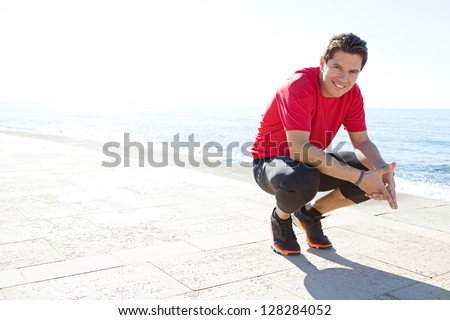 Portrait of a sports man crouching down on a track by the sea on a sunny day, smiling against a blue sky.