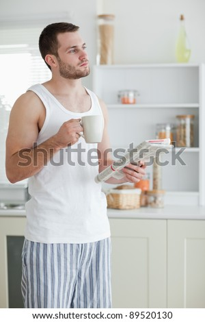 Portrait of a sports man drinking tea while reading the news in his kitchen