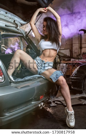portrait of a sporty woman in jeans and top on a background of pink    smoke. Girl model in stylish sportswear in colorful bright neon lights  sitting on open trunk in disassembled car in the garage.  stock photo