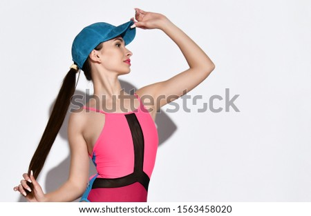 Portrait of a sporty young brunette in sportswear, tight-fitting sports swimsuit with geometric patterns, a blue cap, holding a cap by the visor, profile photo