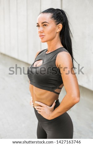 Portrait of a sporty young woman in stylish leggings. Stylish fitness girl on gray background of city streets.