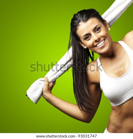 portrait of a sporty young woman with towel against a green background