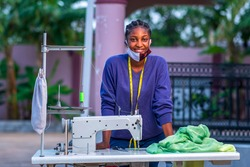 Portrait of a standing Pretty African seamstress wearing a homemade mask in coronavirus pandemic season,working in outdoor,looking successful - concept on African entrepreneurship