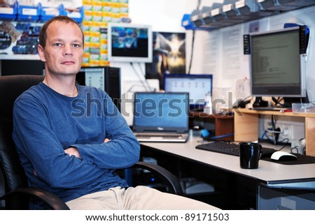 Portrait of a stern looking computer technician in an untidy repair shop, with various computers, screens and hardware components in the background