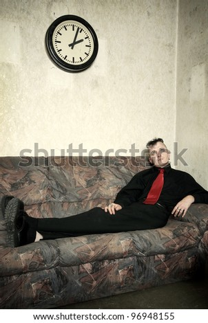 portrait of a strange businessman on an old couch
