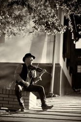 Portrait of a street musician man in a hat with a violin in the city.