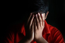 Portrait of a stressed Asian boy in front of black background. An Indian melancholy boy is thinking. Sadness expression of an Asian boy scared and alone. Young Asian boy close his face by hands.