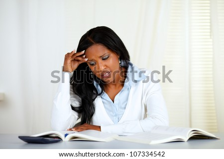 Portrait of a stressed young black woman reading a book at home indoor