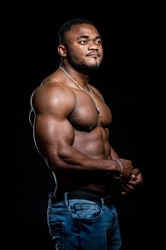 Portrait of a strong afro-american man showing off his physique against black background. Shirtless male model with his hands on hips.