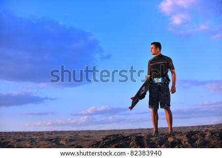 Portrait of a strong young  kitsurf  man at beach on sunset in a contemplative mood with a surfboard