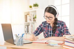 Portrait of a student learning on line with headphones and laptop taking notes in a notebook sitting at her desk at home. mixed race asian chinese model.