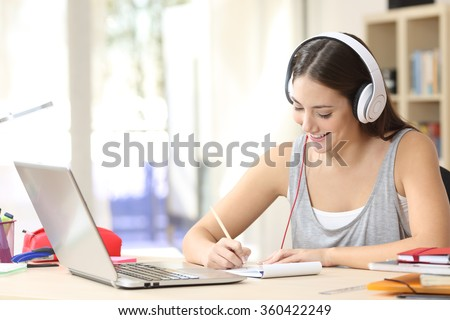 Portrait of a student learning on line with headphones and laptop taking notes in a notebook sitting at her desk at home