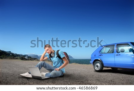 Portrait of a student sitting on the asphalt in front of a seascape and using a laptop