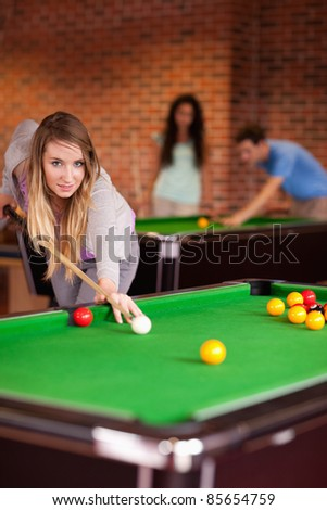 Portrait of a student woman playing snooker in a student home