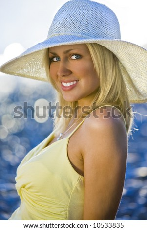 Portrait of a stunningly beautiful young blond woman sitting on the beach wearing a hat and bathed in sunshine while the sun glistens off the sea behind her