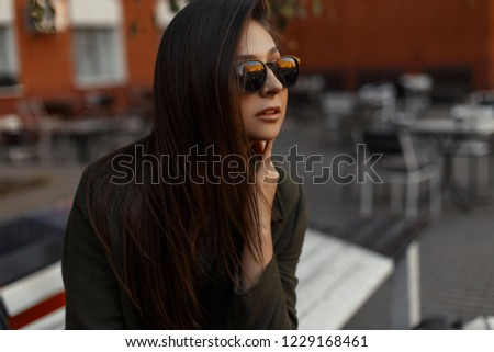 Portrait of a stylish and young brunette girl wearing a green coat and sunglasses, sitting outdoors against a background of a street cafe. Outdoor lifestyle. Fashionable woman. #1229168461