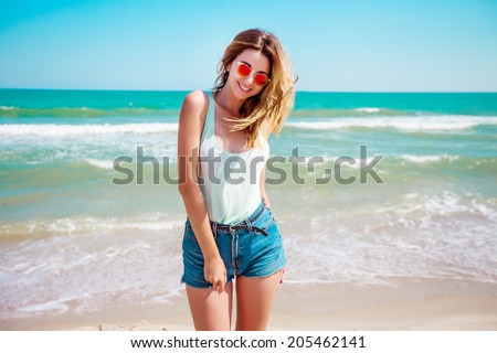 Portrait of a stylish sexy girl in sunglasses and jeans shorts. Resting on a paradise beach, enjoying the sun.