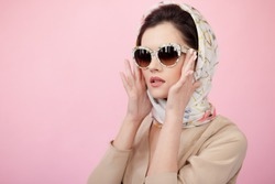 Portrait of a stylish woman posing in sunglasess and scarf on head, isolated on pink background.Horizontal view.
