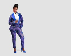 Portrait of a stylish young African woman wearing a stylish blue African print pant suit standing against a grey background