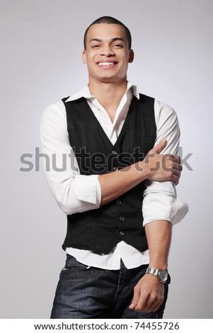 Portrait of a stylish young fashion male model on gray background.