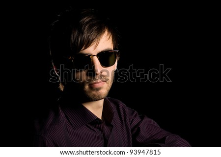 Portrait of a stylish young man wearing sunglasses on a black background