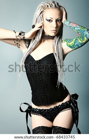 Portrait of a stylish young woman with white dreadlocks in black lingerie. Fashion.