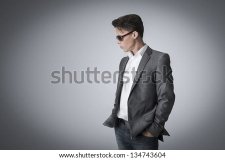 Portrait of a suave handsome man in a stylish suit and sunglasses standing sideways with his hands in his pockets lost in though on a grey background with corner vignetting and copy space