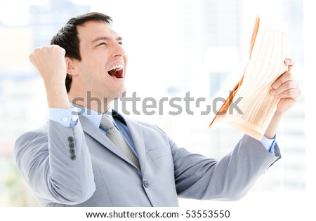 Portrait of a successful businessman reading a newspaper in the office - stock photo