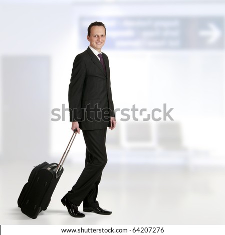 Portrait of a successful businessman walking through airport with travel bag