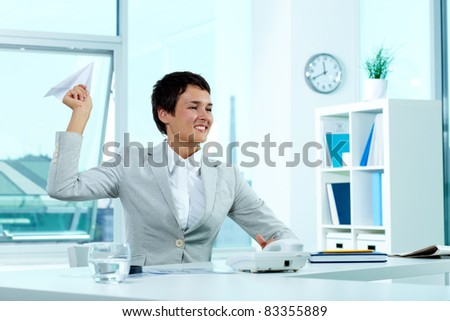 Portrait of a successful employer at workplace holding paper plane - stock photo