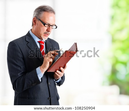Portrait of a successful handsome businessman looking at his agenda
