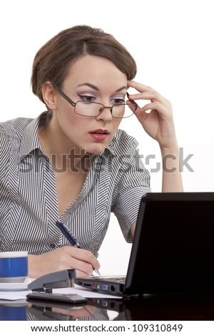 Portrait of a successful young business woman wearing glasses working on a notebook at office.