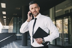 Portrait of a successful young businessman dressed in formal clothes standing outside a glass building with folder and talking on mobile phone