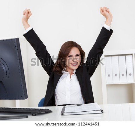 Portrait of a successful young businesswoman with clenched fists at computer desk
