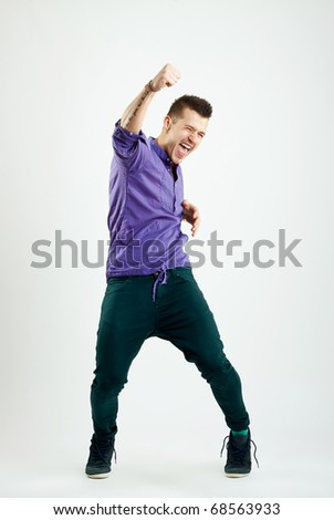 Portrait of a successful young fashion man with his hand raised