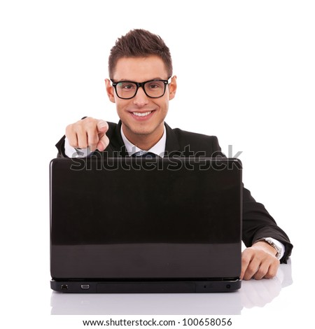Portrait of a successful young male entrepreneur at his desk working on laptop and pointing to you