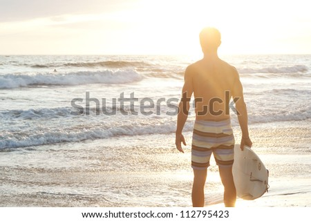 portrait of a surfer on the beach with surfboard