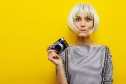 Portrait of a surprise girl with a camera in hand on a yellow background. Isolated studio. Blonde girl.