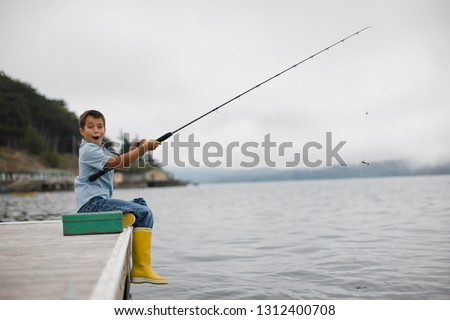 Portrait of a surprised boy fishing off the side of a jetty with a fishing rod.