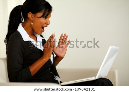 Portrait of a surprised executive young woman reading a great business news on laptop while sitting on couch