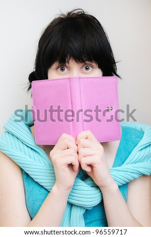Portrait of a surprised young woman with diary