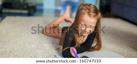 Portrait of a sweet charming young girl who draws with his coloring at home